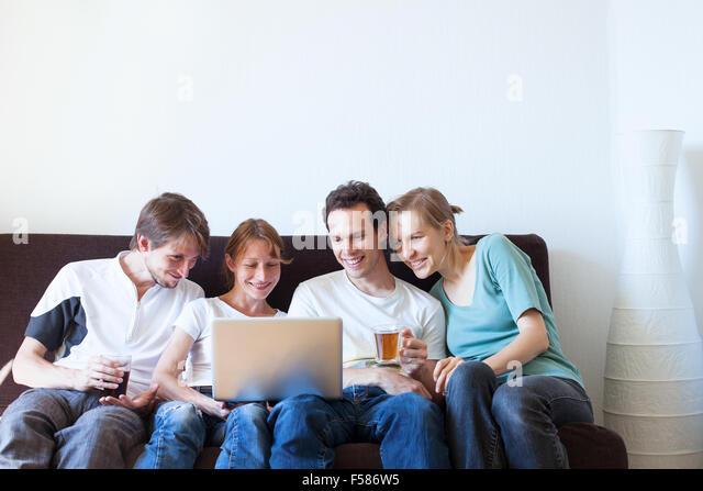 Gruppe von Freunden vor dem Fernseher und lächelnd Stockbild
