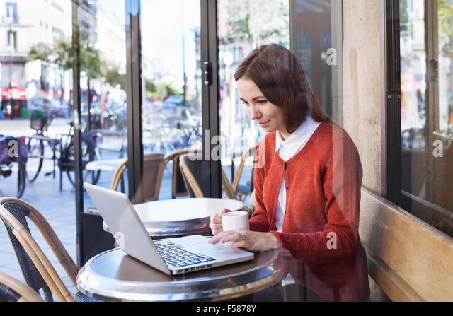 junge Frau mit Laptop im café Stockbild