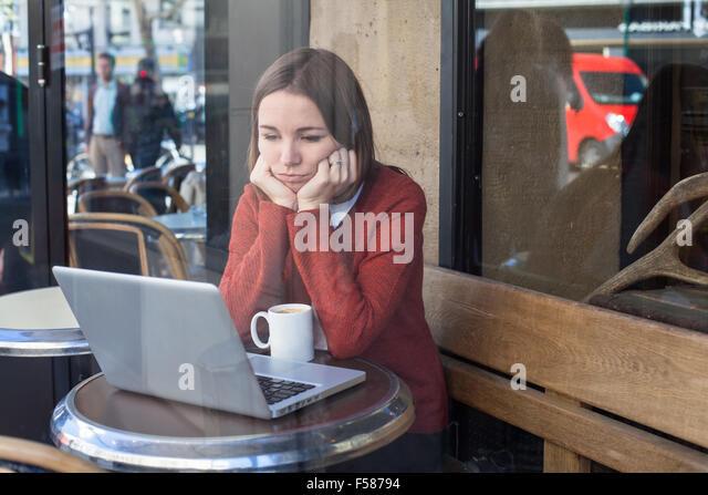 Neid-Konzept, gelangweilt traurige Frau vor computer Stockbild