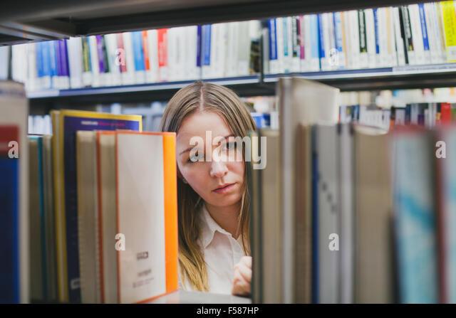 Studentin, die Auswahl des Buches in der Bibliothek Stockbild