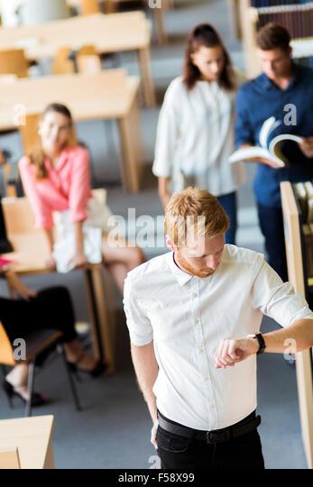 Gruppe von Jugendlichen, die Vorbereitung auf eine Exame in einer Bibliothek und haben nicht viel Zeit übrig. Stockbild