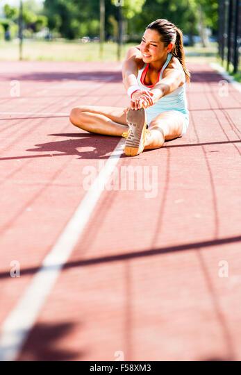 Schöne junge sportliche Frau erstreckt sich im Sommer vor der Ausführung Stockbild
