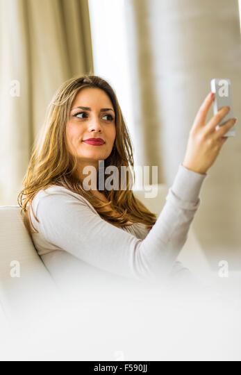 Schöne Brünette mit einem Telefon in einem stilvollen Haus und smyling Stockbild