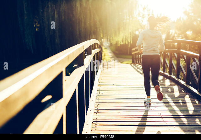 Schöne weibliche Jogger läuft während des Sonnenuntergangs über Brücke Stockbild