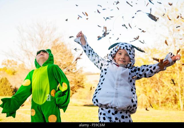Zwei jungen im Kostüm fangen und werfen Blätter Stockbild