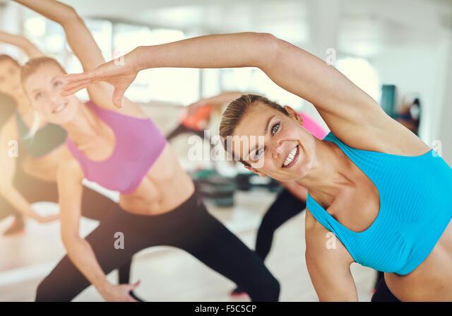 Fitness, Sport, Training und Lifestyle Konzept - Gruppe der lächelnden Frauen Stretching in der Turnhalle Stockbild