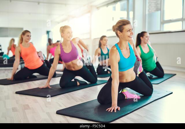 Fitness, Sport, Training und Lifestyle-Konzept - Gruppe von lächelnden Frauen im Fitness-Studio Stockbild