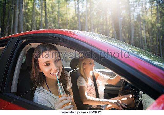 Junge Freunde trinken Soda in Auto Stockbild