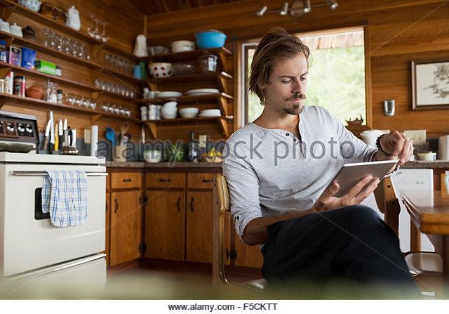 Mann mit digital-Tablette am Küchentisch Kabine Stockbild