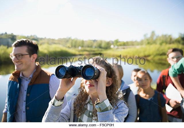 Neugierigen Schulmädchen mit dem Fernglas auf Exkursion Stockbild