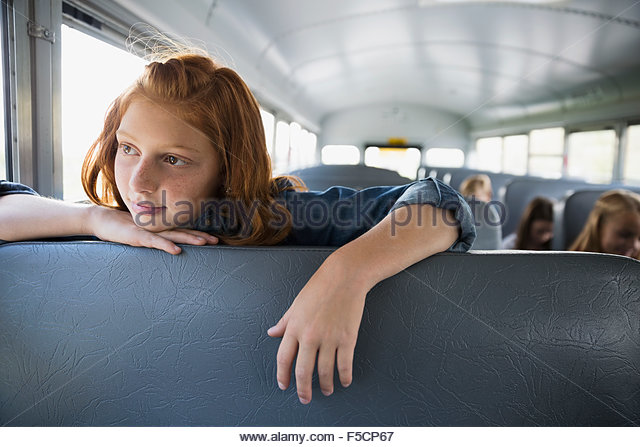 Nachdenklich Schulmädchen wegsehen auf Schulbus Stockbild