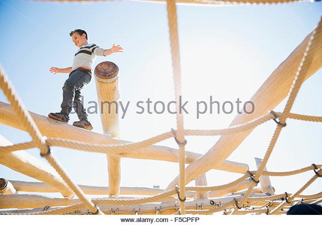 Junge balancing auf Baumstamm über net sonnige Spielplatz Stockbild