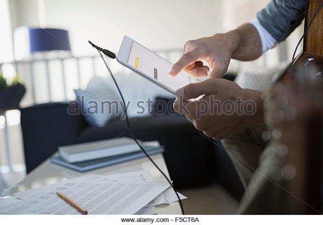 Mann mit Gitarre Musikaufnahmen mit digital-Tablette Stockbild