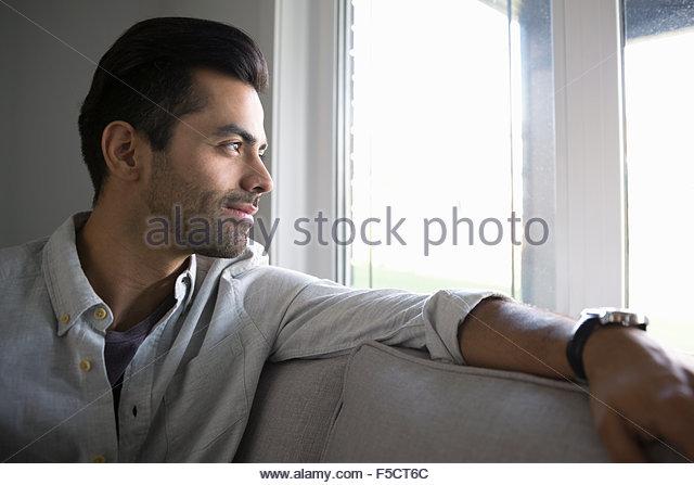 Nachdenklicher Mann auf Sofa Blick aus Fenster Stockbild