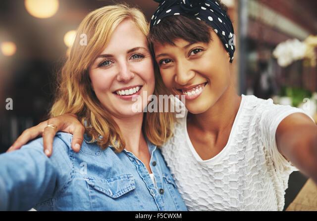 Zwei junge Frauen, die besten Freunde sitzen, Arm in Arm mit dem Gesicht nah zusammen lächeln in die Kamera, Stockbild
