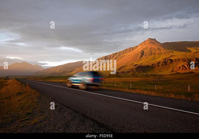 SUV auf Route 1 (Ringstraße) und Berglandschaft in der Nähe von Hofn, Island Stockbild