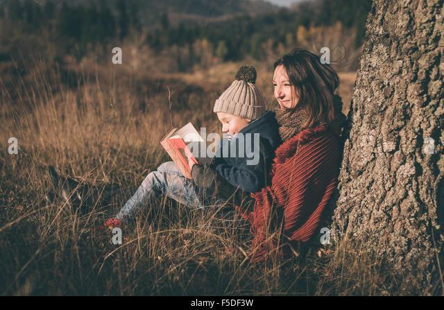 Mutter und Sohn in der Natur. Lesebuch und lächelnd. Stockbild