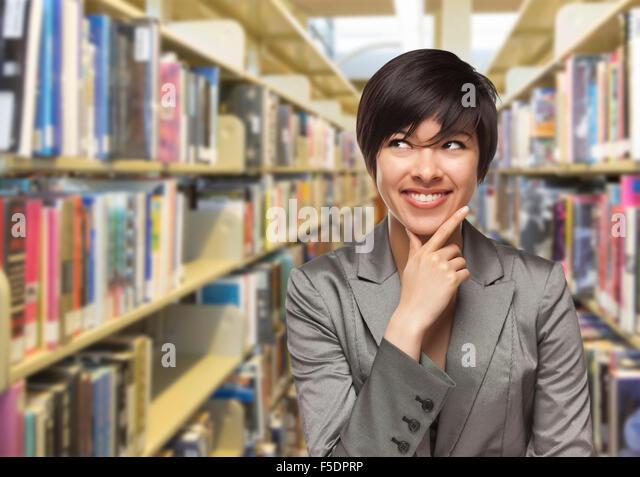 Neugierige Mischlinge Mädchen auf der Suche auf die Seite in der Bibliothek. Stockbild
