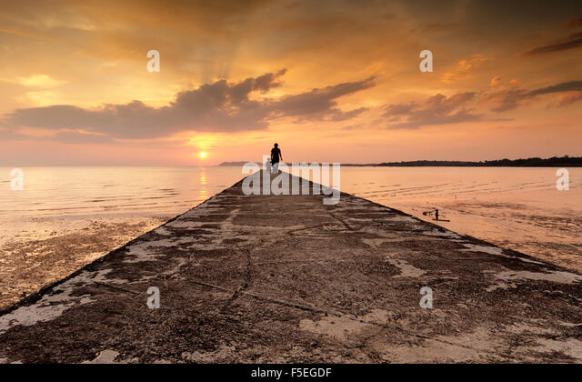 Silhouette eines Mannes und seines Sohnes am Ende von einem Steg, Port Dickson, Malaysia Stockbild