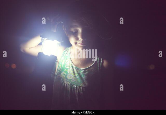Mädchen halten Lampe in der Dunkelheit Stockbild