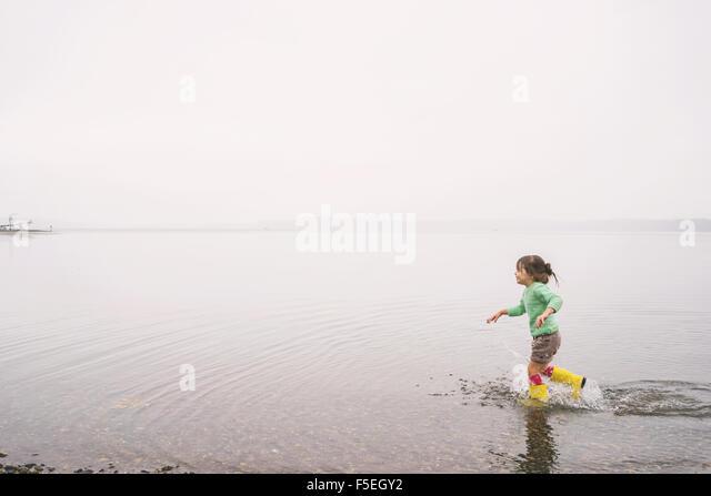Mädchen im flachen Wasser laufen Stockbild