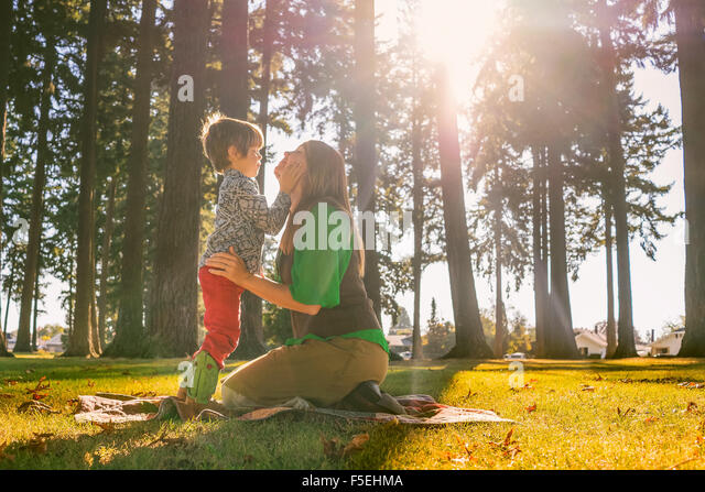 Mutter und Sohn berühren mit lächelnden Gesichtern Stockbild