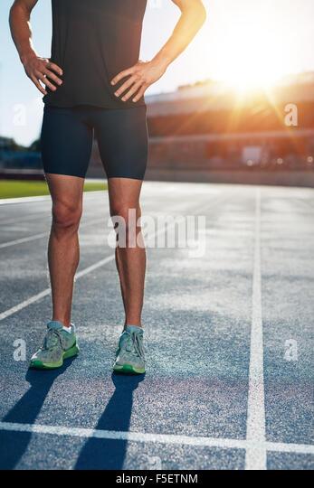 Niedrige Abschnitt Schuss der Athlet Mann auf Rennen verfolgen mit seinen Händen auf den Hüften. Schuss Stockbild