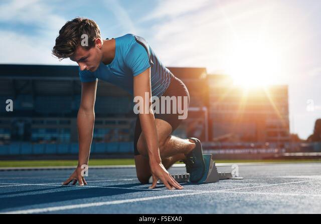 Junge männliche Athlet im Startblock auf Laufstrecke. Junger Mann in die Ausgangsposition für den Betrieb Stockbild