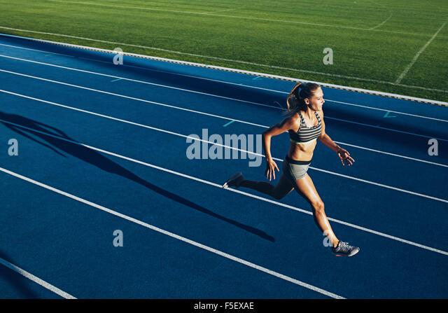Junge Frau läuft auf Rennstrecke während der Trainingseinheit. Weibliche Läufer üben auf Leichtathletik Stockbild