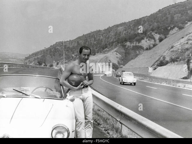 Ein Mann mit einem weißen Alfa Romeo Giulietta Stockbild