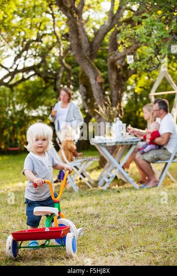 Familie mit drei Kindern (12-17 Monate, 2-3) in Hinterhof, Havdhem, Gotland, Schweden Stockbild