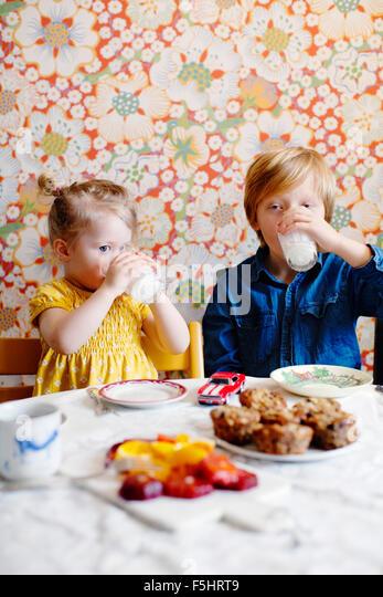 Schweden, junge (10-11) und Mädchen (2-3) Trinkmilch Stockbild