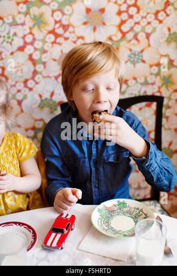 Schweden, junge (10-11) und Mädchen (2-3) essen Kuchen Stockbild
