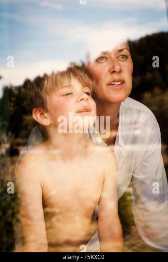 Schweden, Halsingland, Jarvso, Mutter und Sohn (4-5) spähen durch Fenster Stockbild
