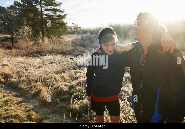 Mutter und Sohn auf Grünland, Sportbekleidung, die Arme umeinander Lächeln auf den Lippen tragen Stockbild