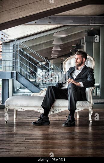 Mitte erwachsenen Mannes tragen Anzug sitzt auf Chaise Lounge wegschauen Stockbild