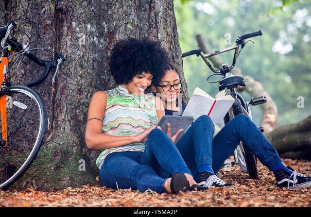 Reife Frau und Sohn sitzen gegen Parkbaum lesen Buch und digital-Tablette Stockbild
