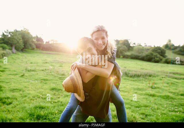 Porträt des jungen Mannes geben Freundin eine Huckepack im ländlichen Bereich Stockbild