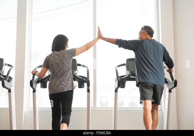 Rückansicht des reifes Paar auf dem Laufband handeln hoch fünf Stockbild