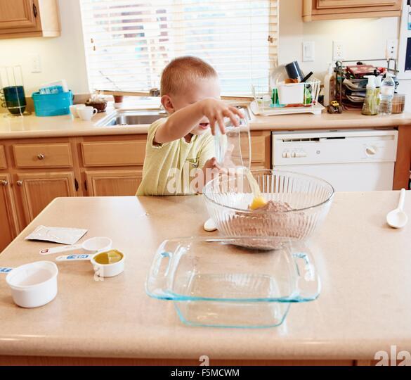 Junge vorbereitet Teig in der Schüssel Stockbild