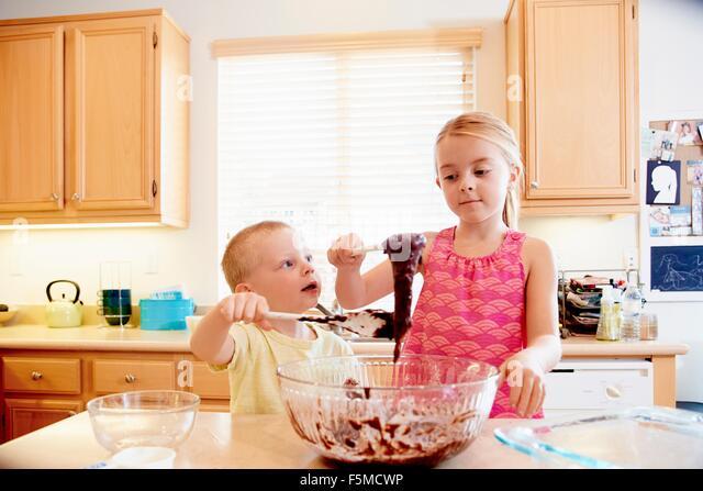 Geschwister, die schmelzende Schokolade in eine Rührschüssel geben - Stock-Bilder