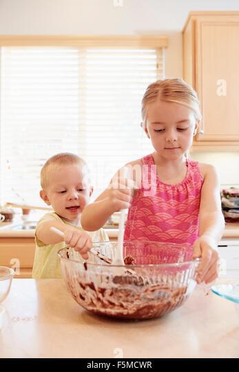 Geschwister, die schmelzende Schokolade in eine Rührschüssel geben Stockbild