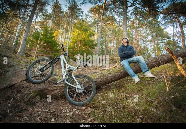 Schweden, Vastergotland, Lerum, Mountainbiker auf Baumstamm sitzend Stockbild