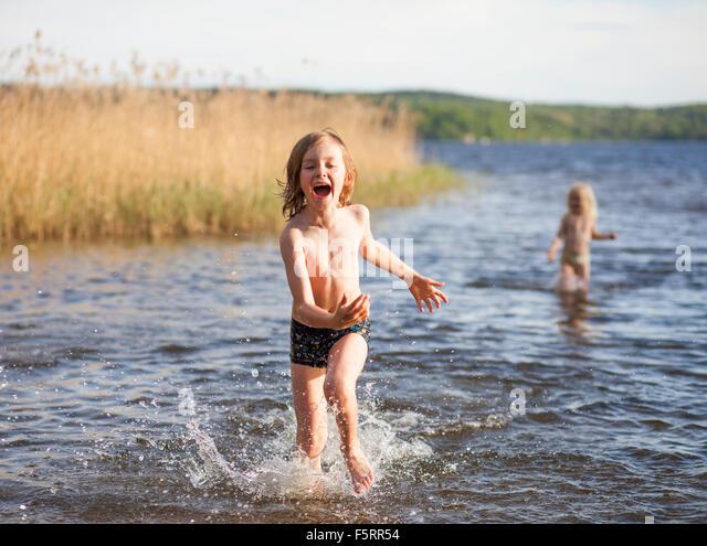Schweden, Vastergotland, Lerum, See Aspen, jungen (8-9) und Mädchen (6-7) spielen im See Stockbild