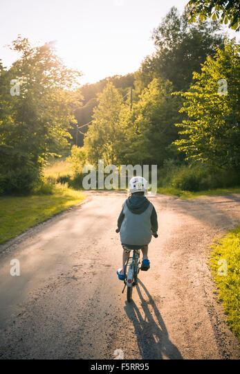 Schweden, Bohuslan, Halleback, Boy (10-11) entfernt auf asphaltierten Straße Radfahren Stockbild