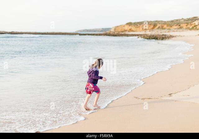 Portugal, Alentejo, Vila Nova de Milfontes, Mädchen (4-5) laufen in surf Stockbild