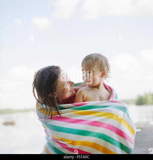 Finnland, Uusimaa, Lapinjarvi, Mutter und Tochter (2-3) in Handtuch gewickelt Stockbild