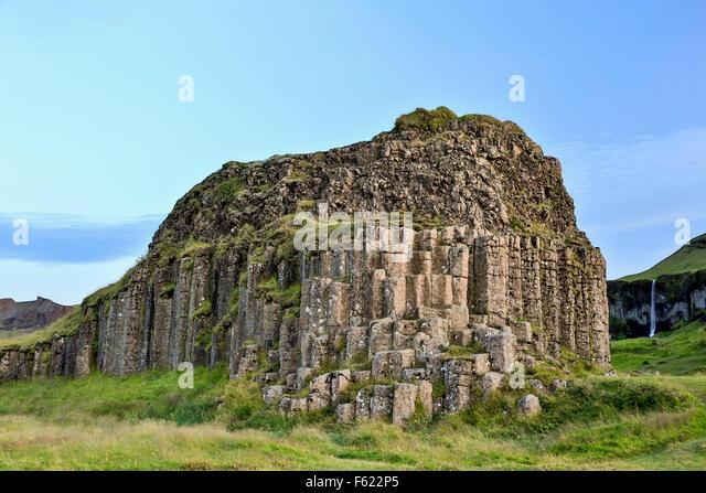Säulenförmigen Basalt Felsen (und Wasserfall im Hintergrund), Dverghamrar (Zwerg Klippen), in der Nähe Stockbild