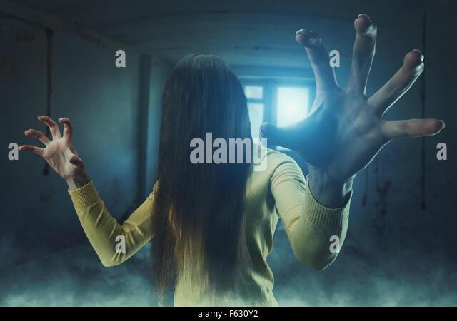 Zombie-Mädchen mit langen Haaren im Gesicht in einem verlassenen Gebäude Stockbild