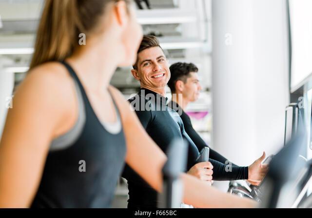 Gut aussehender Mann und schöne junge Frau mit einem Stepper im Fitness-Studio und ein Gespräch Stockbild